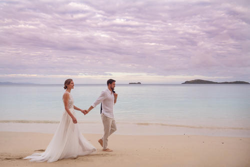 Newlyweds walking together along the beach at Kokomo Private Island Fiji