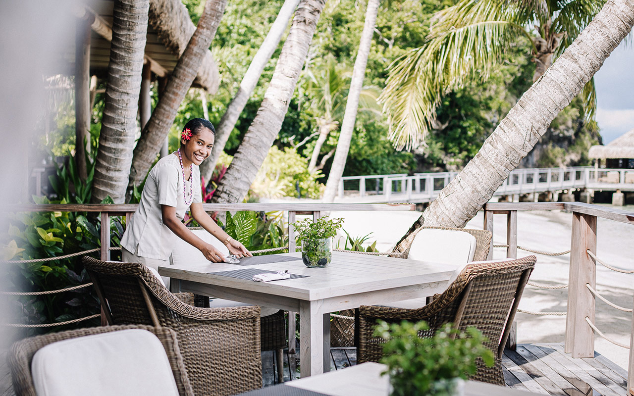 Staff memeber setting an outdoor table up for dining at Kokomo Private Island Fiji
