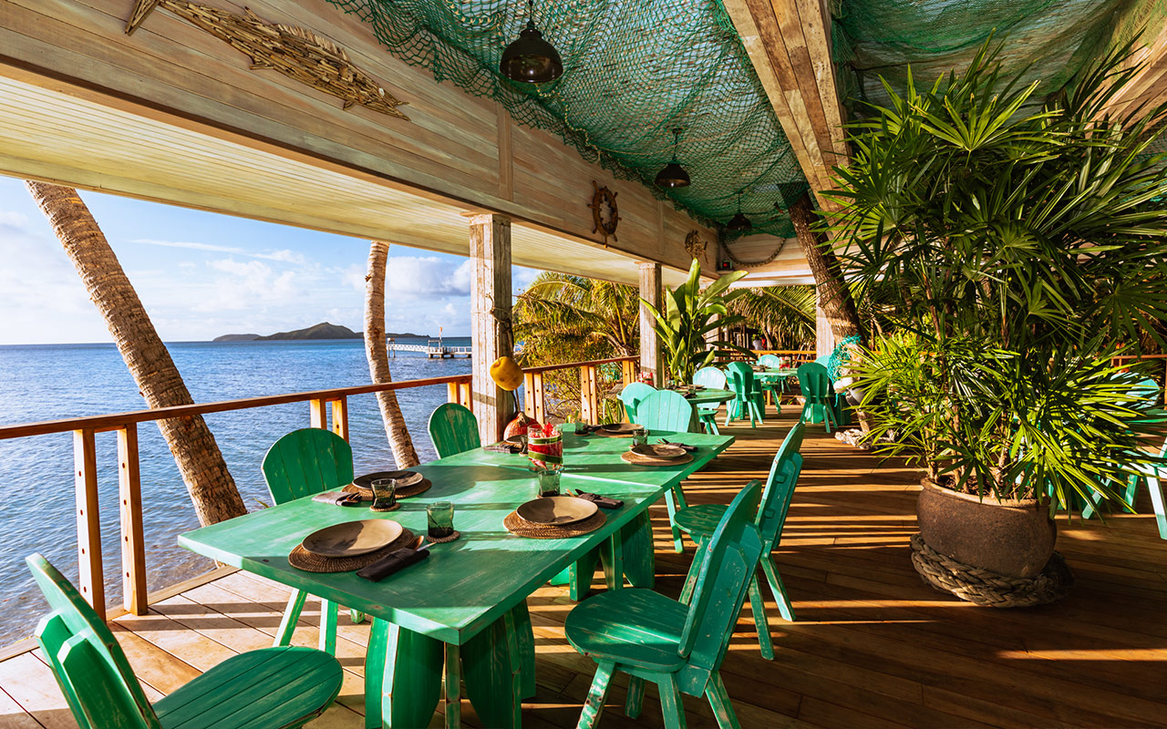 Walker D'Plank with dining tables set up overlooking the ocean at Kokomo Private Island Fiji