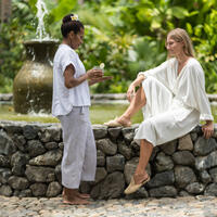 A Yaukuve Spa Sanctuary therapist passing a fresh health drink to a guest at Kokomo Private Island Fiji