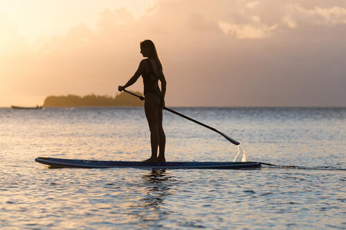 A guest stand-up paddleboarding in front of the sunset in the waters surrounding Kokomo Private Island Fiji