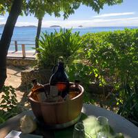 A bucket holding bottles of health drink on a beachside table at Kokomo Private Island Fiji