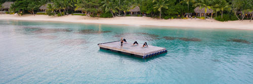 A guest practicing yoga outdoors at Kokomo Private Island Fiji