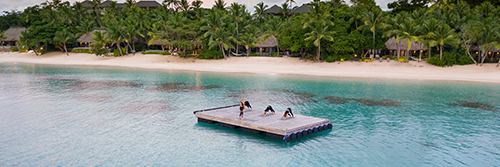 Guests in a yoga session on a floating pontoon at Kokomo Private Island Fiji